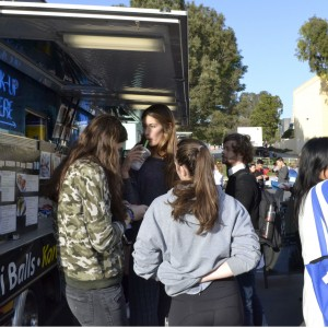 Students gathered around food trucks at the first Hoemcoming carnival.