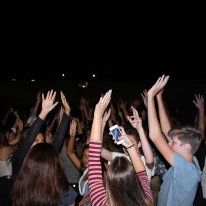 Students raise their hands up in the air as they dance to the music.